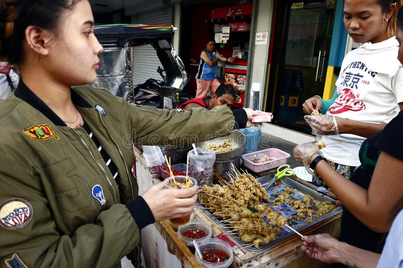 Customers buy assorted street food such as chicken intestine and other innards royalty free stock photos