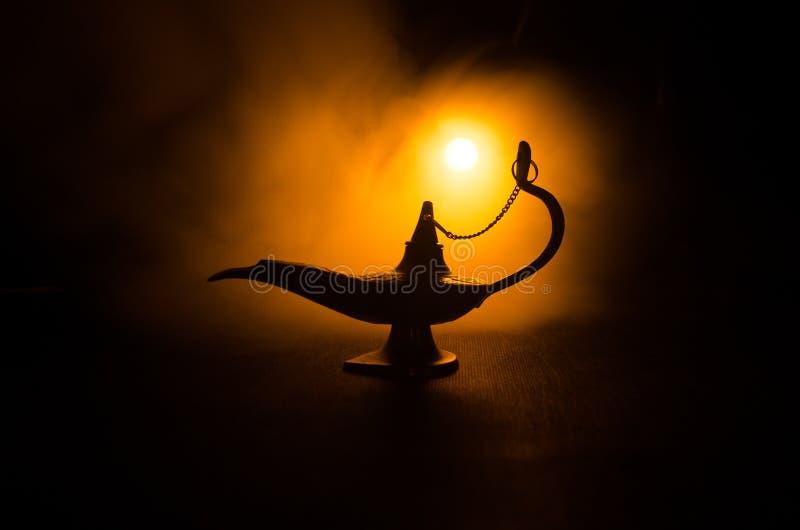 Antique Aladdin arabian nights genie style oil lamp with soft light white smoke, Dark background. Lamp of wishes concept. Toned. Antique Aladdin arabian nights stock photos
