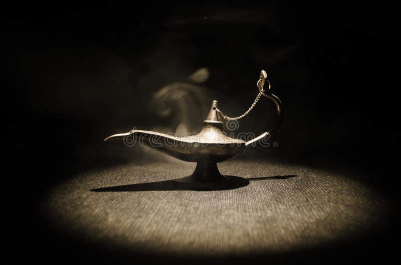 Antique Aladdin arabian nights genie style oil lamp with soft light white smoke, Dark background. Lamp of wishes concept. Toned. Antique Aladdin arabian nights stock photo