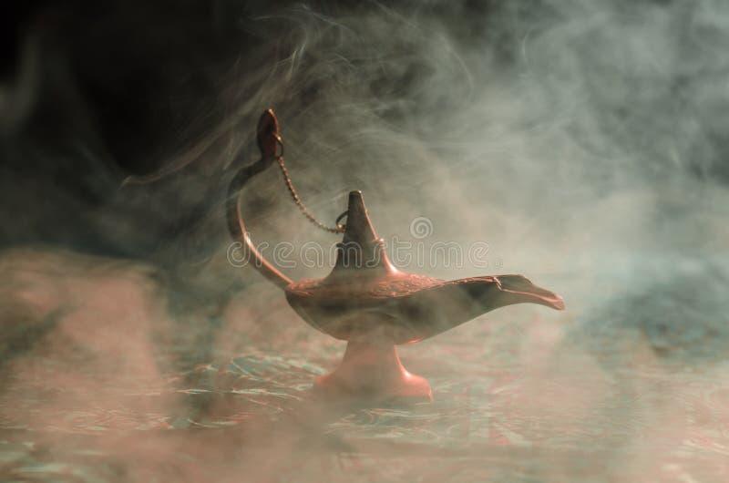 Antique Aladdin arabian nights genie style oil lamp with soft light white smoke, Dark background. Lamp of wishes concept. Toned. Antique Aladdin arabian nights royalty free stock photography