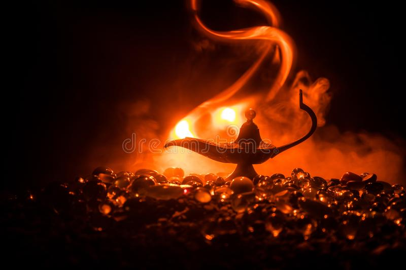 Antique Aladdin arabian nights genie style oil lamp with soft light white smoke, Dark background. Lamp of wishes concept royalty free stock photo