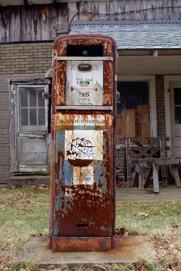 Antique American gas pump. Rusted and with chipped off paint in front of a old brick building stock photo