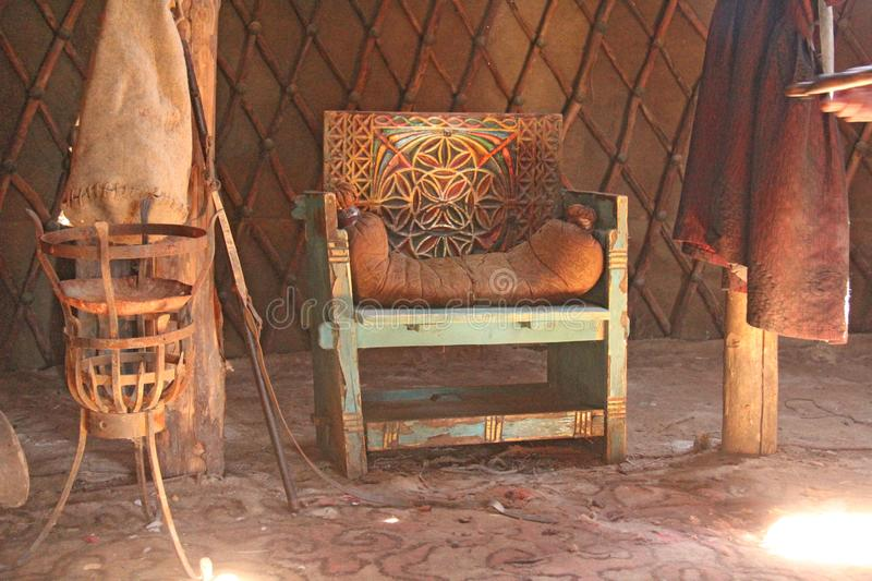 An antique or ancient wooden armchair with leather trim in the sun. Beautiful wooden interior. Sarai Batu stock images