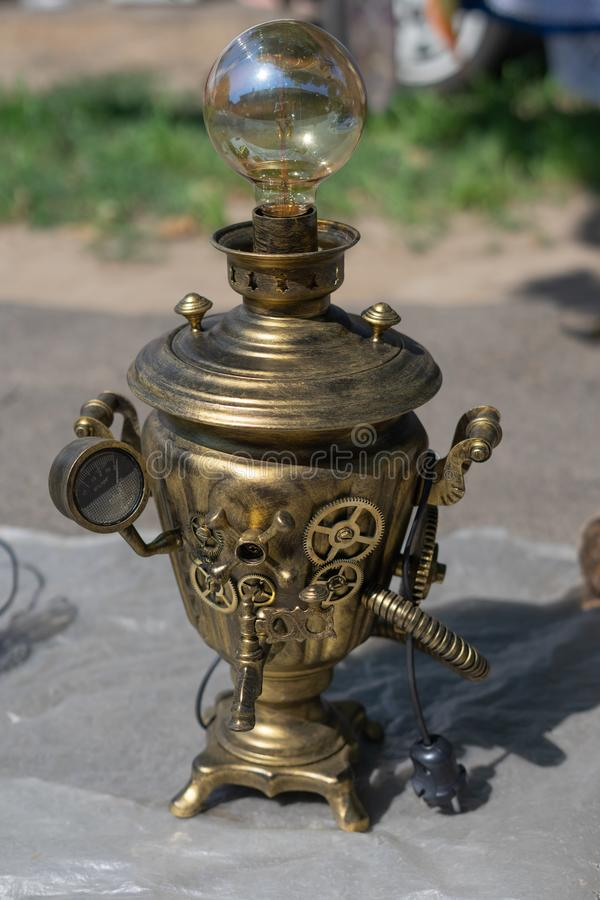 Antique antiques are sold at a flea market.Copper samovar, reworked under the lamp royalty free stock images