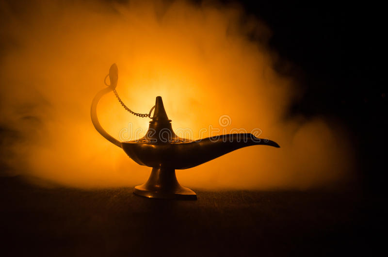 Antique arabian nights style oil lamp with soft light white smoke, Dark background. Lamp of wishes concept. Toned royalty free stock photo