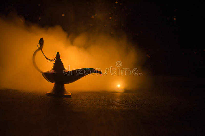 Antique arabian nights style oil lamp with soft light white smoke, Dark background. Lamp of wishes concept. Toned royalty free stock photography