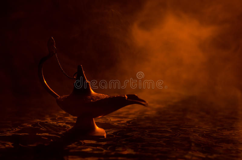 Antique arabian nights style oil lamp with soft light white smoke, Dark background. Lamp of wishes concept. Toned stock images