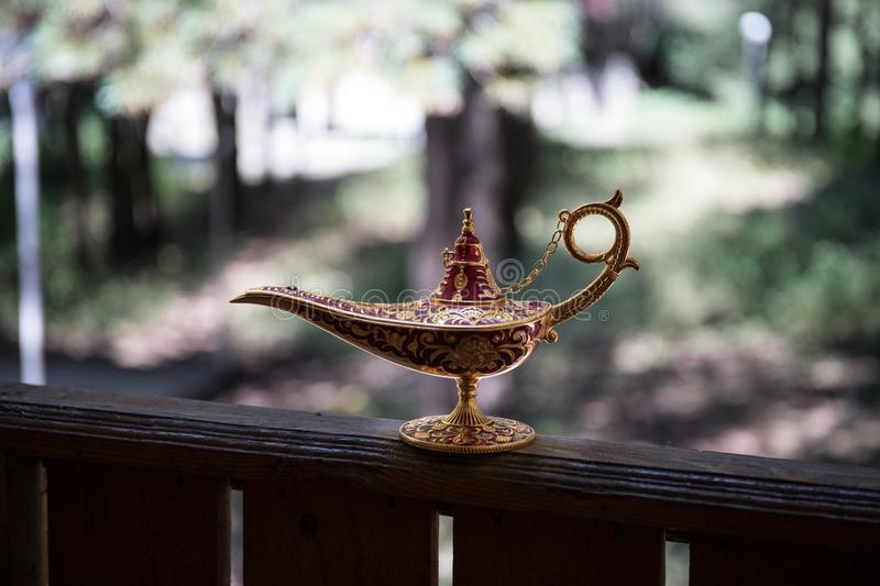 Antique artisanal Aladdin Arabian nights genie style oil lamp at the forest. Lamp of wishes fantasy concept. Selective focus stock image