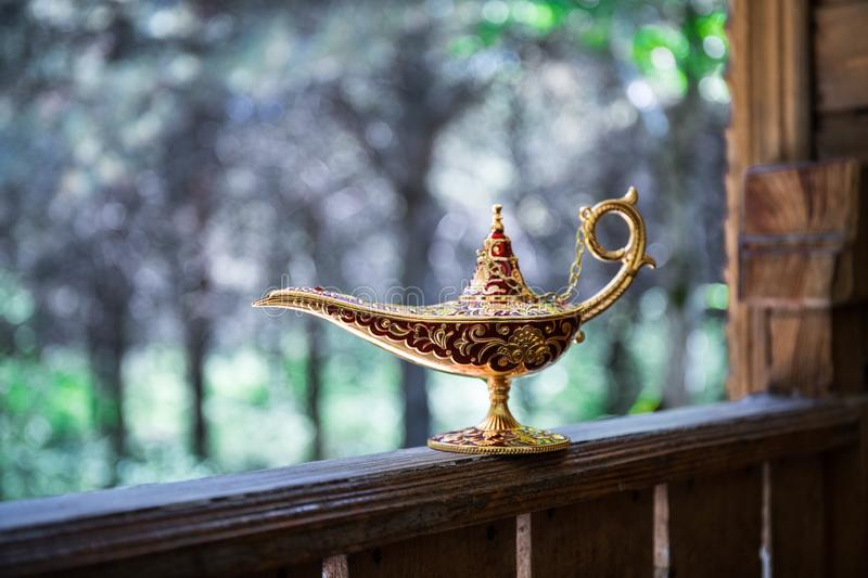 Antique artisanal Aladdin Arabian nights genie style oil lamp at the forest. Lamp of wishes fantasy concept. Selective focus royalty free stock photo