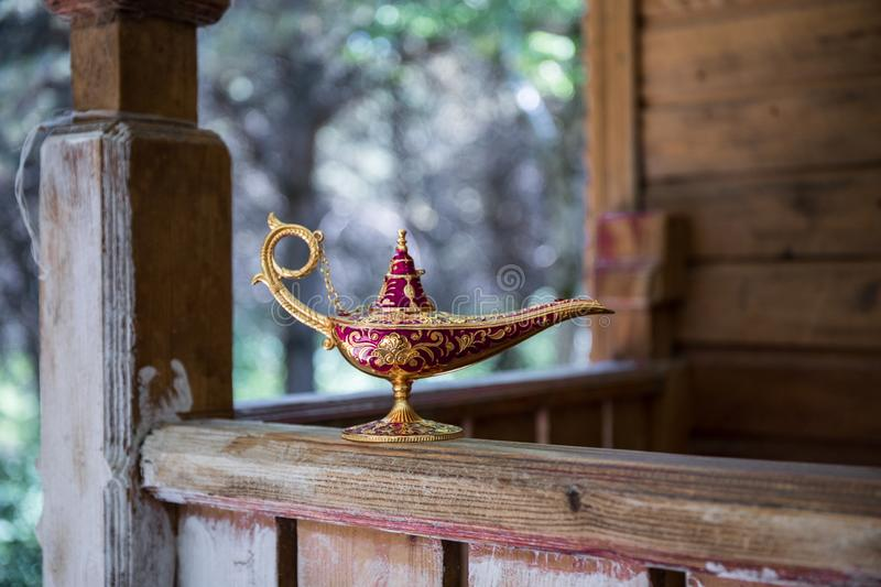 Antique artisanal Aladdin Arabian nights genie style oil lamp at the forest. Lamp of wishes fantasy concept. Selective focus royalty free stock photography