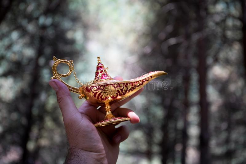 Antique artisanal Aladdin Arabian nights genie style oil lamp at the forest. Lamp of wishes fantasy concept. Selective focus stock images