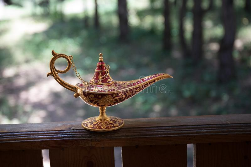 Antique artisanal Aladdin Arabian nights genie style oil lamp at the forest. Lamp of wishes fantasy concept. Selective focus stock photos
