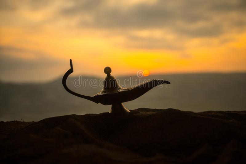 Antique artisanal Aladdin Arabian nights genie style oil lamp with soft light white smoke. Sunset background. Lamp of wishes stock photo