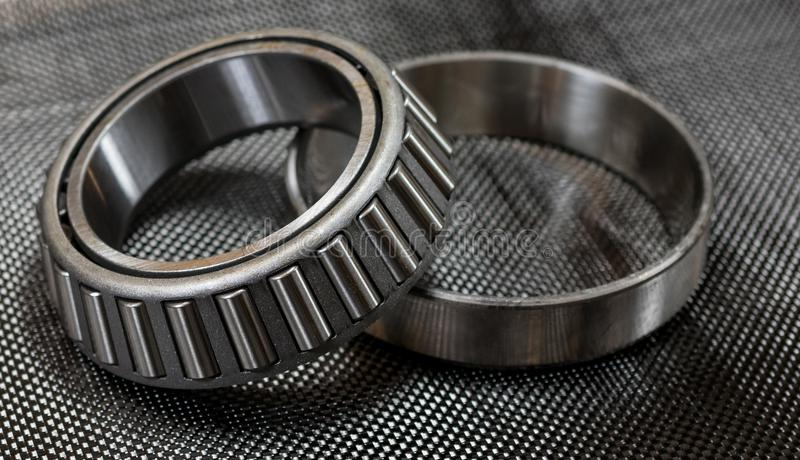 Automotive tapered roller bearing and race on carbon fiber cloth royalty free stock photos