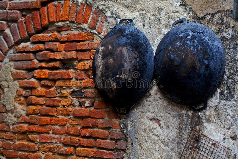 Two old frying pan hanging on the red rough brick wall royalty free stock images