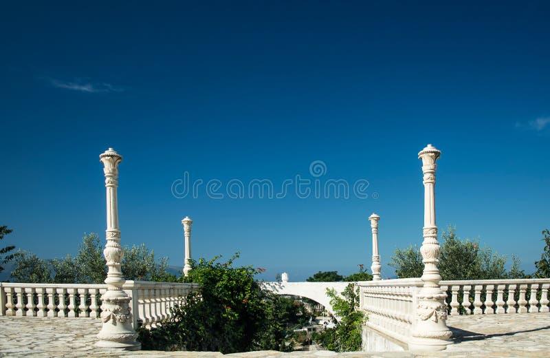 Antique balustrade with entrance to the garden and clear blue sk stock photos