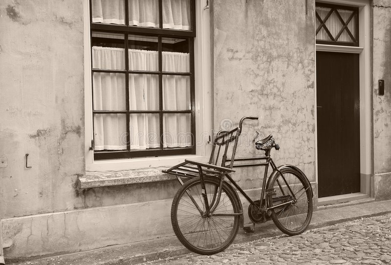 Antique bicycle. Against house -sepia royalty free stock photos