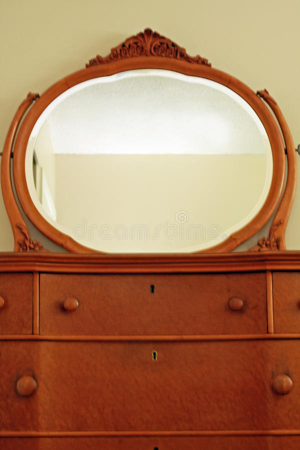 Antique bird's eye maple dresser and mirror. Antique bird's eye maple wood dresser with mirror and top two drawers royalty free stock photos