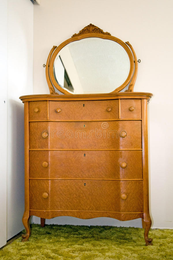 Antique bird's eye maple dresser with mirror. Antique bird's eye maple dresser with oval mirror, light wood royalty free stock photography