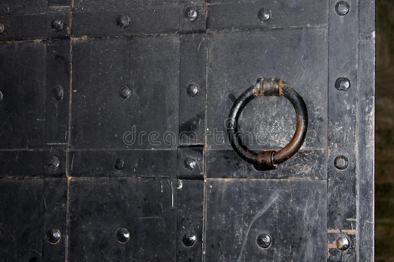 Antique black upholstered in metal forged gate door fragment of Staraya Ladoga, Russia stock photography