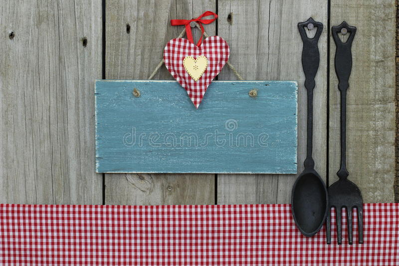 Antique blank blue sign with heart, gingham tablecloth and cast iron spoon and fork. Antique blank blue sign with gingham heart and tablecloth, cast iron spoon stock images