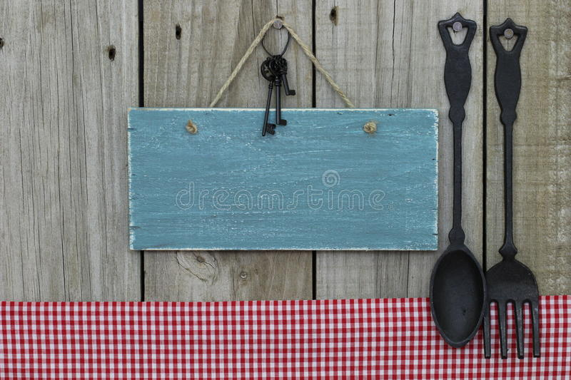 Antique blank blue sign with iron keys, gingham tablecloth and cast iron spoon and fork hanging on wooden background. Antique blank blue sign with three iron royalty free stock photography