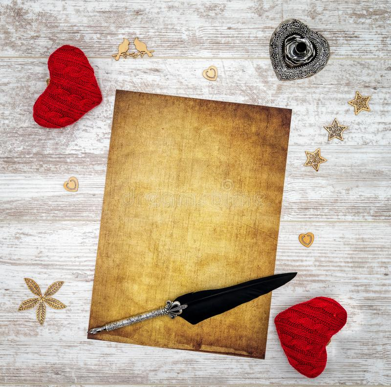 Blank vintage Valentine`s Day card with red cuddle hearts, wooden decorations, ink and quill - top view stock photography