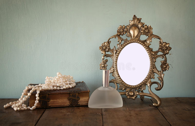 Antique blank Victorian style frame and old book with vintage pearl necklace on wooden table. retro filtered image stock photo