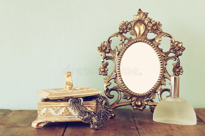 Antique blank victorian style frame, perfume bottle and neckless on wooden table. retro filtered image. Template, ready to put photography stock photos