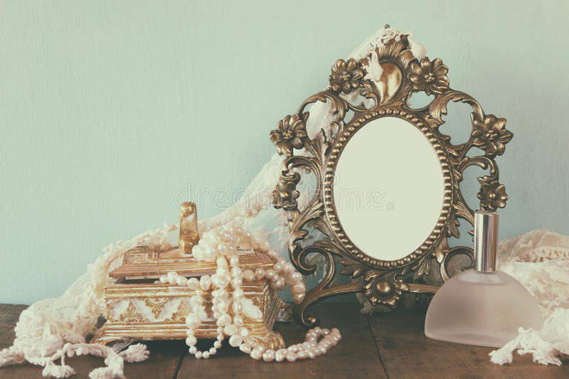 Antique blank victorian style frame, perfume bottle and white pearls on wooden table. retro filtered and toned. Template, ready to put photography stock photos