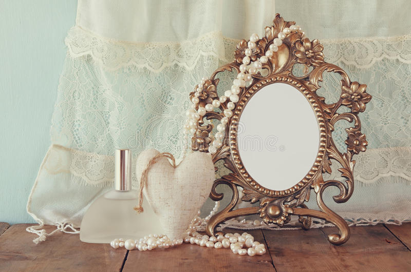 Antique blank victorian style frame, perfume bottle and white pearls on wooden table. retro filtered and toned. Template, ready to put photography stock photography