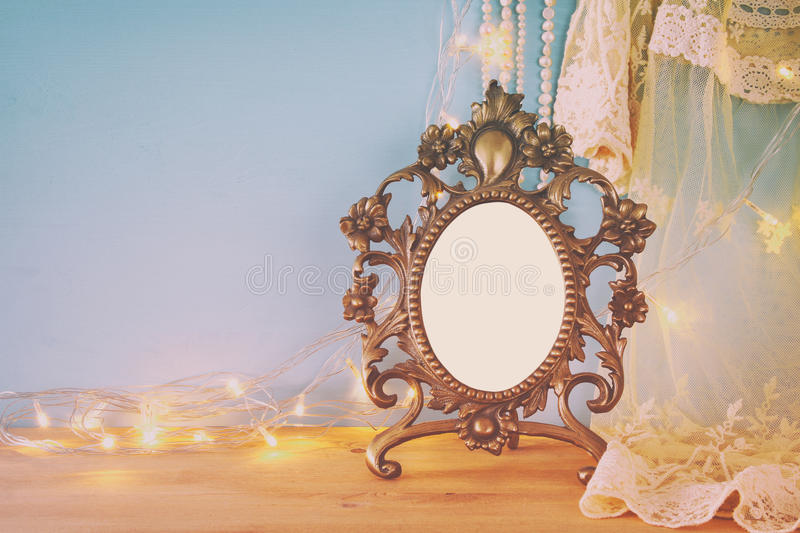 Antique blank victorian style frame on wooden table. Template, ready to put photography. Filtered image stock photography