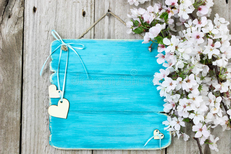 Antique blue sign with white flowers and wood hearts hanging on wooden fence royalty free stock image
