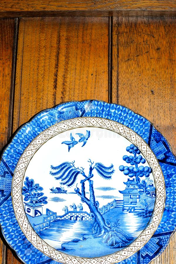 Antique blue and white willow pattern china plate. On a plate dresser stock photos