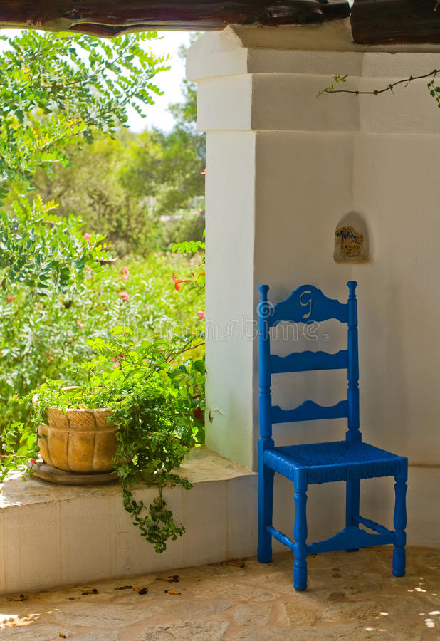 Antique Blue Wooden and Wicker Chair in a Porch stock images
