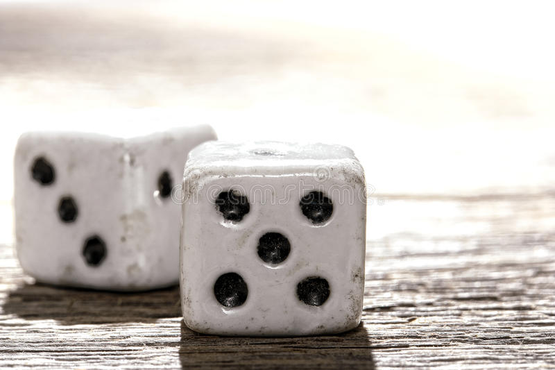 Antique Bone Craps and Wager Shooting Dice on Wood. Antique bone craps game and wager gambling lucky shooting dice on old weathered wood table royalty free stock photos