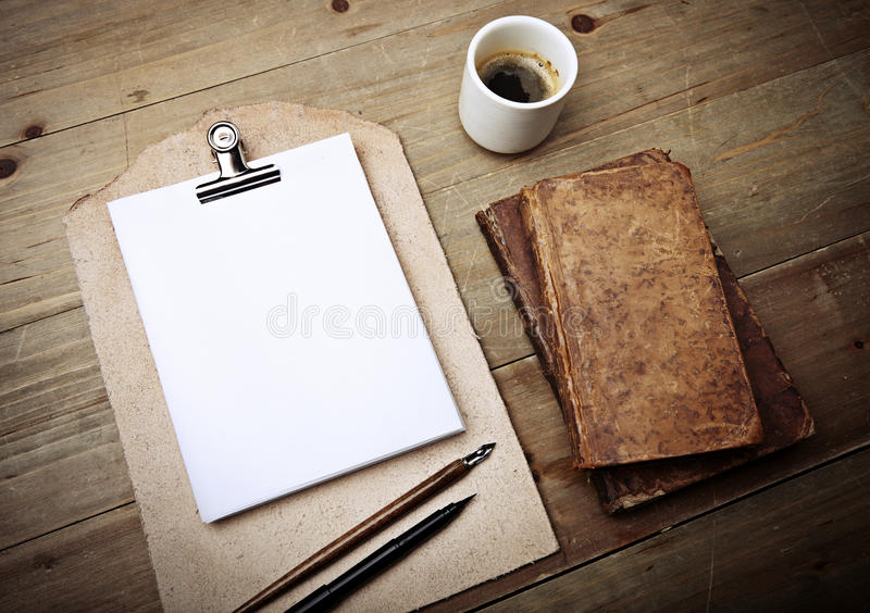 Antique books, cup of coffee and vintage leather clipboard stock image