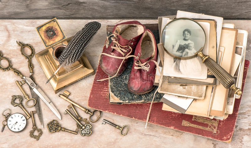 Antique books and photos, keys, writing accessories and baby shoes royalty free stock image