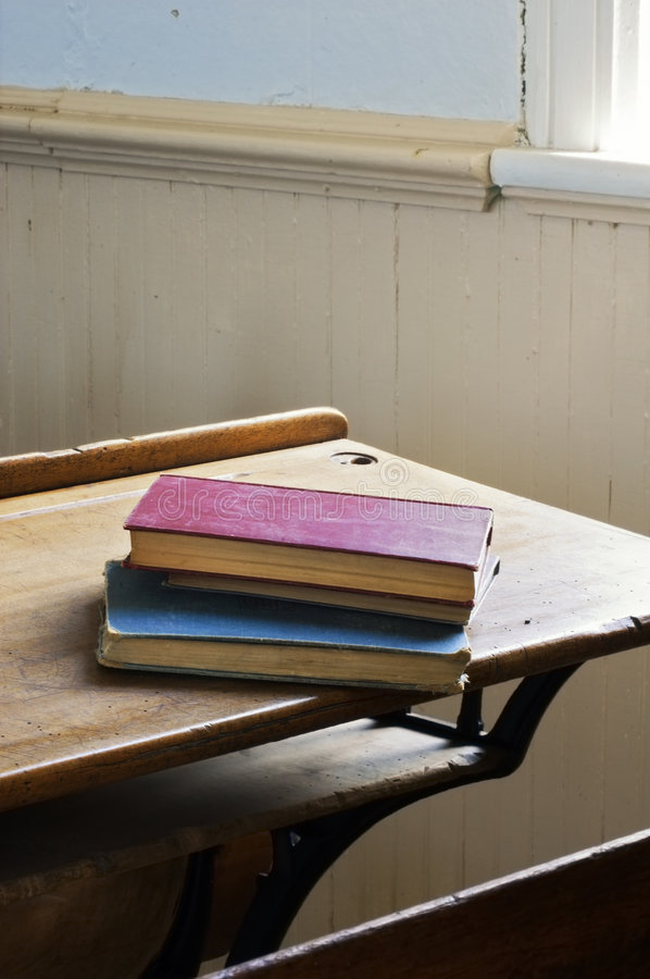 Antique Books Stacked on School Desk Dramatic Light royalty free stock photography