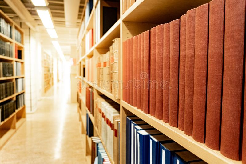 Antique books on wooden bookshelf in library. Antique leather cover books on wooden bookshelf with aisle perspective in university public library. Reading stock photo