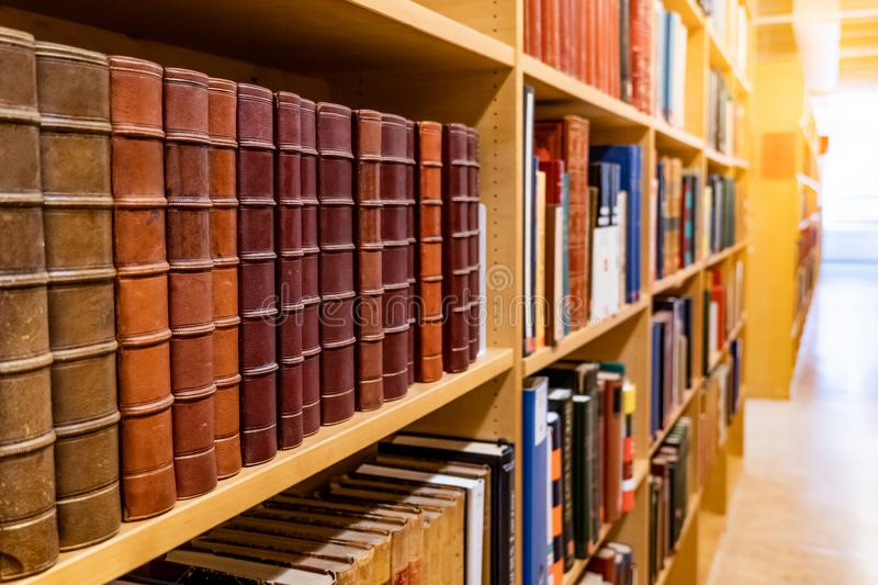 Antique books on wooden bookshelf in library. Antique leather cover books on wooden bookshelf with aisle perspective in university public library. Reading royalty free stock photography