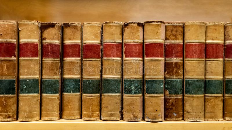Antique books on wooden bookshelf in library. Antique leather cover books on wooden bookshelf in university public library. Reading philosophy or history royalty free stock images