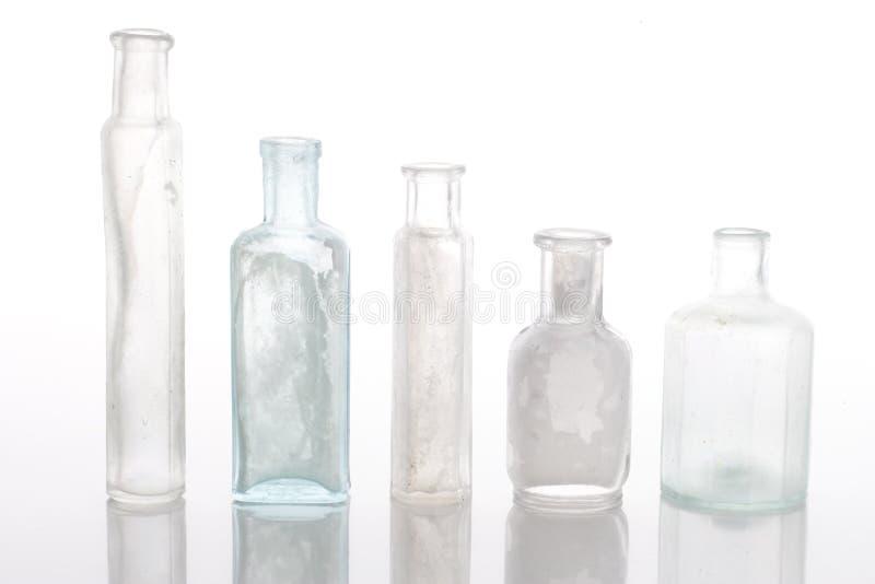 Antique bottles on white table stock photos