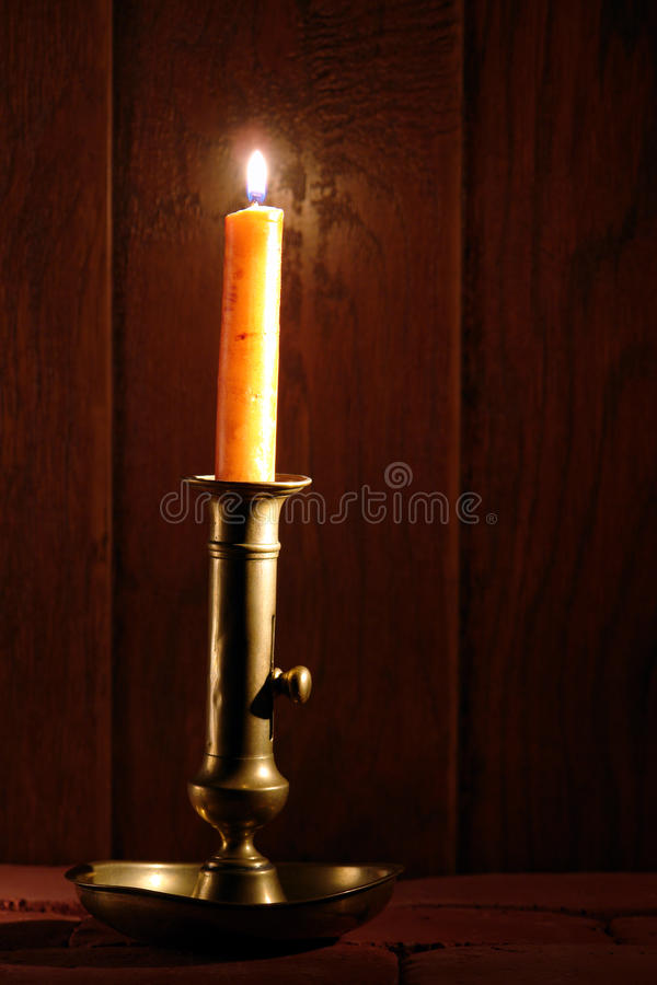 Antique Brass Candlestick with Candle Burning royalty free stock images