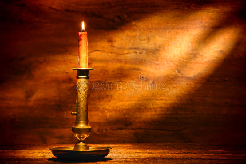 Antique Brass Candlestick Candleholder with Candle. Old antique brass candlestick adjustable candleholder with vintage handmade artisan natural wax candle stock image