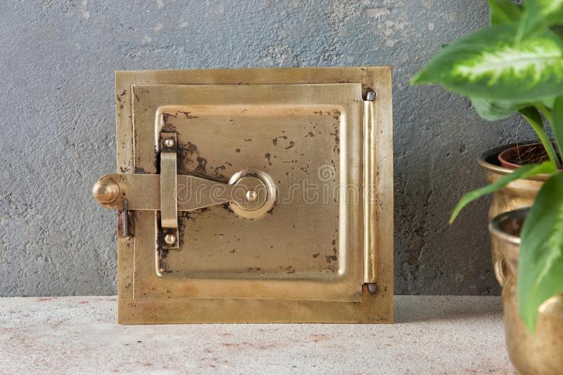 Antique brass chimney flap on gray stock image