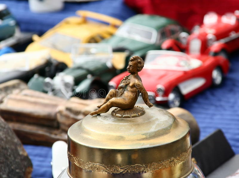 Antique brass figurine by toy cars. Small brass figure of a child or angel sits on an ornate brass canister by retro toy cars stock photos
