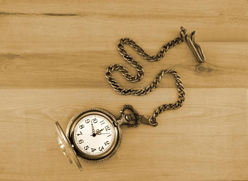 Antique brass metal pocket watch with chain displayed on a wood background. This photograph with an overhead perspective features an antique brass copper metal stock photo