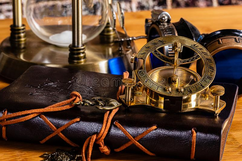 An Antique Brass Nautical Compass and Sundial, with a leather journal, goggles and a brass hourglass stock images