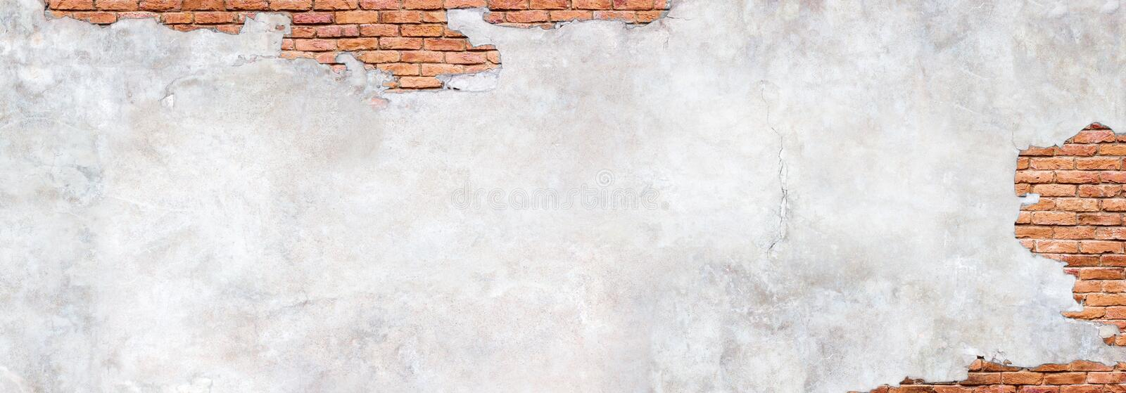 Antique brick wall under damaged plaster. Weathered brickwork texture with cracked concrete. Damaged plaster on brick wall background. Brickwork under crumbling stock image